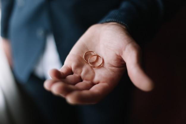Handen van bruidegom met ringen. trouwdag, bruid en bruidegom. bruiloft details