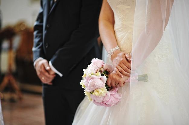 Handen van bruidspaar in de kerk