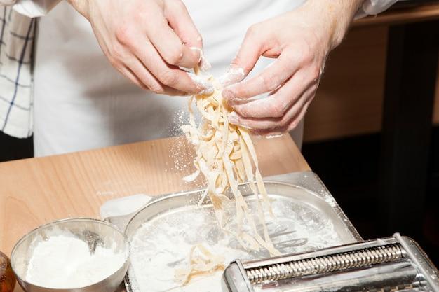 Handen van chef-kok die een portie van fettuccine maakt. detailopname.