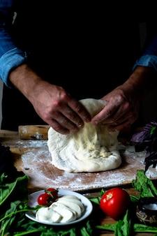 Handen van chef-kok italiaanse chef-kok koken pizza man handen koken pizza deeg voor pizza koks handen