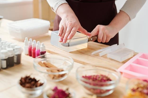 Handen van craftswoman met mes snijden stuk van grote stuk harde zeep massa op houten bord tijdens het werken in de studio