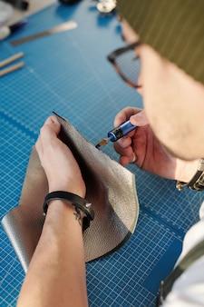 Handen van creatieve leerbewerker in armband zitten door blauwe tafel en verwerking van randen van grijs leerstuk met krijt