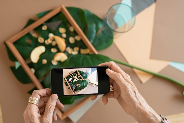 Handen van creatieve rijpe vrouw met smartphone nemen foto van samenstelling in houten frame bestaande uit appelschijfjes op groen blad