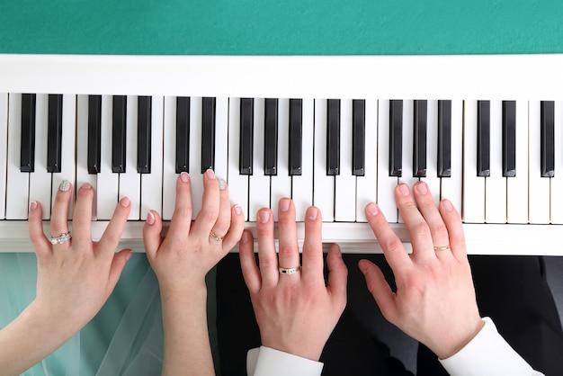 Handen van de bruid en bruidegom die piano spelen