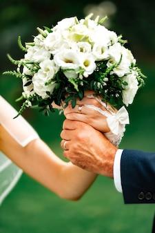 Handen van de bruid en bruidegom houden een boeket delicate witte rozen vast op valentijnsdag of bruiloft