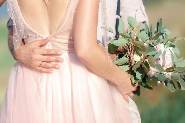 Handen van de bruid en bruidegom met bruiloft boeket bloemen. fijne kunstfotografie.