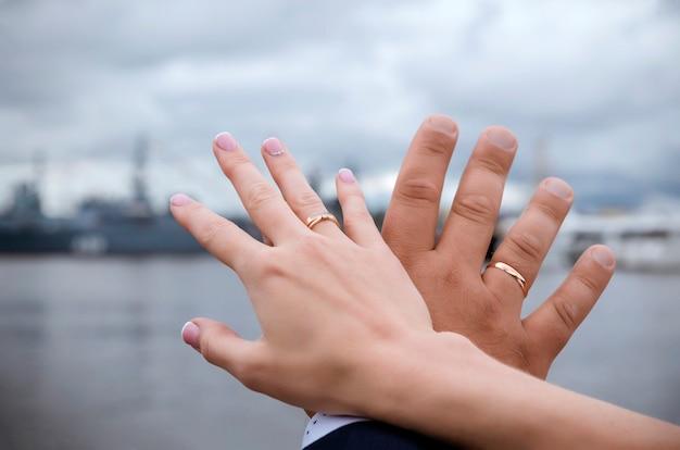 Handen van de bruid en bruidegom met gouden trouwringen op het oppervlak van water met boten en lucht met wolken op een bewolkte dag