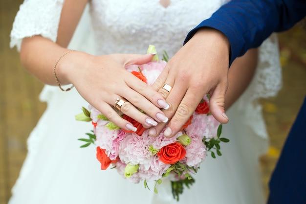Handen van de bruid en bruidegom met ringen op een bruiloft boeket