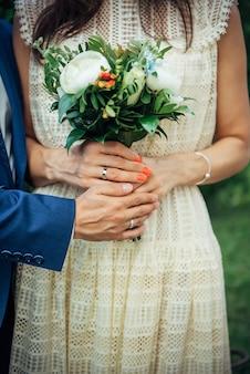 Handen van de bruid en bruidegom met trouwringen, boeket verse bloemen, vintage kanten jurk