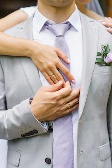 Handen van de bruid en bruidegom met trouwringen.