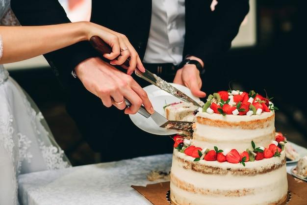Handen van de bruid en bruidegom snijden bruidstaart
