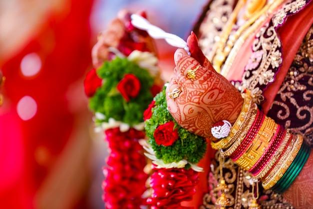 Handen van de bruid zijn prachtig versierd met indiase mehndi-kunst samen met sieraden en kleurrijke armbanden