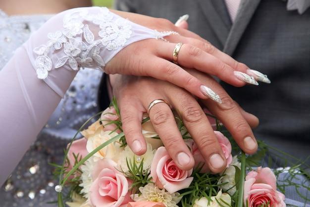 Handen van de bruidegom en de bruid op achtergrond van huwelijksboeket