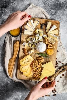 Handen van de chef-kok met een kaasschotel geserveerd met noten en vijgen. grijze achtergrond. bovenaanzicht