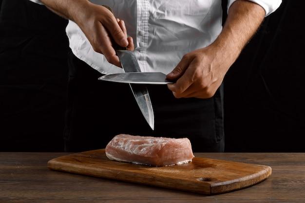Handen van de chef scherpt een keukenmes