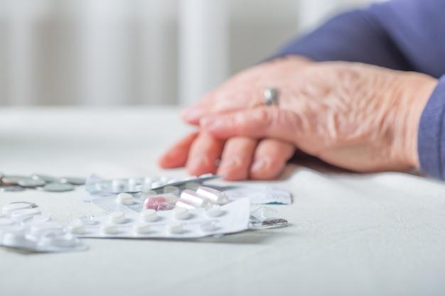 Handen van de close-up de hogere vrouw met pillen en muntstukken op lijst thuis. een oudere gepensioneerde telt geld.