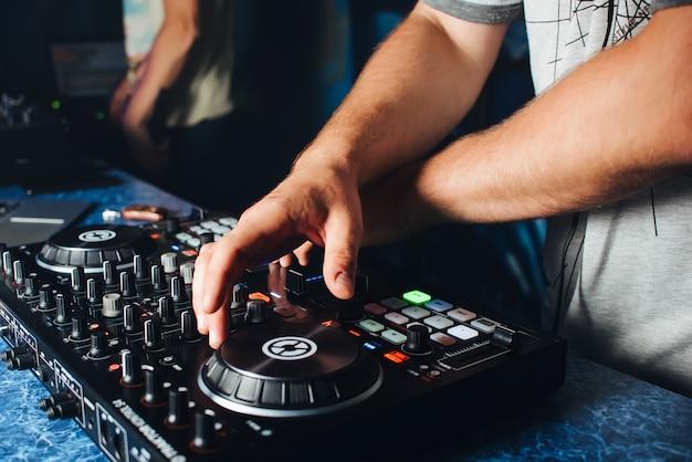 Handen van de dj op de mixer