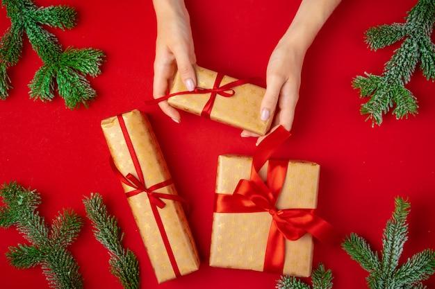 Handen van de doos van de kerstmisgift van de vrouwenholding op een rood