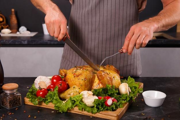 Handen van de hoofdman gesneden gebakken kip met groenten