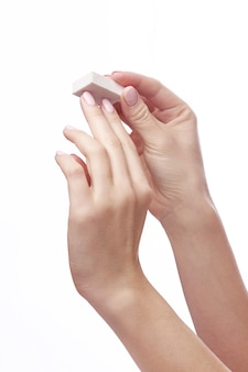 Handen van de jonge nagelvijl van de vrouwenholding over wit