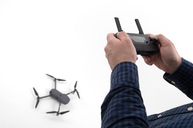 Handen van de man die het bedieningspaneel op de quadcopter vasthoudt
