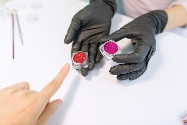 Handen van de manicure toont glitters voor nagels