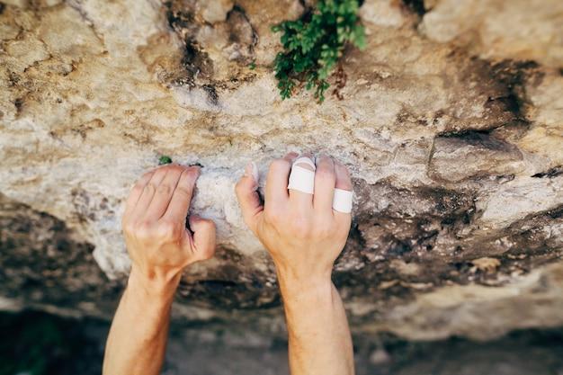 Handen van de mannelijke rotsklimmer die op de klip hangen