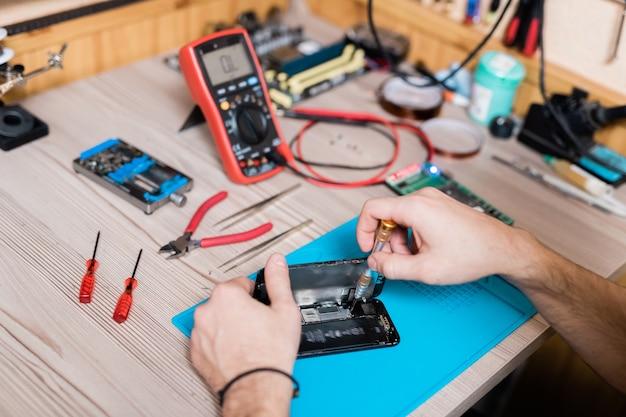 Handen van de meester van de gadgetreparatieservice met behulp van een schroevendraaier tijdens het repareren van kleine details van de gedemonteerde smartphone