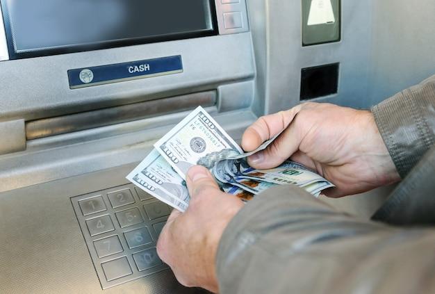 Handen van de mens die amerikaanse dollarbankbiljetten tellen bij atm