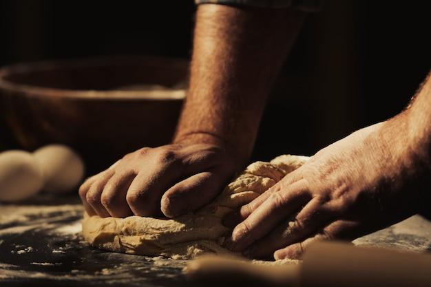 Handen van de mens die deeg kneedt in de keuken, close-up