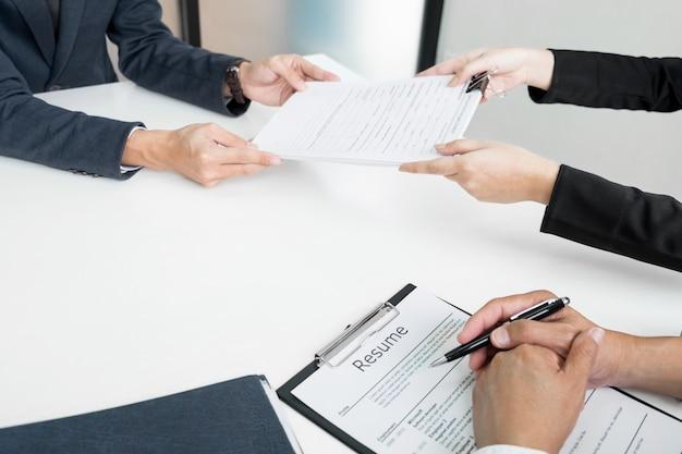 Handen van de mens die een portefeuille geven aan de hr-man in kantoor voor een interview.