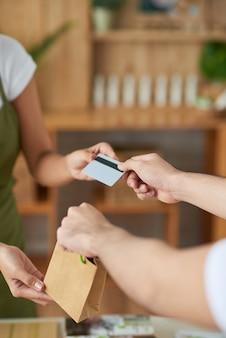 Handen van de mens die handgemaakte zeep koopt in de offline winkel en met creditcard betaalt