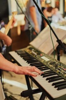 Handen van de mens die het pianameisje spelen die het synthesizertoetsenbord spelen