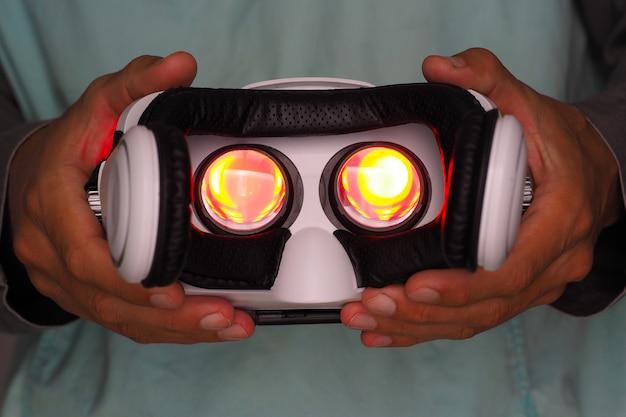 Handen van de mens die virtuele werkelijkheidsbeschermende brillen houden. rood licht binnen.