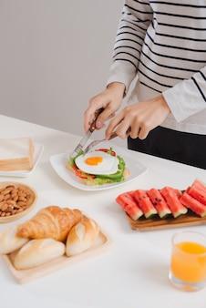 Handen van de mens snijden de eieren op papier, geserveerd met brood, kruiden, worst en vers sap.