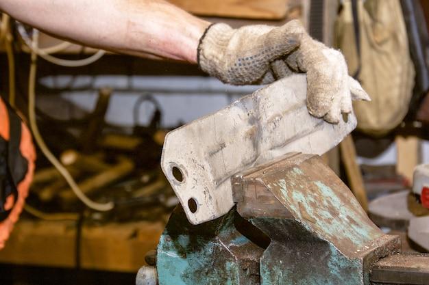 Handen van de monteur in vuile handschoenen worden vastgeklemd in een bankschroef van de machine in dienst