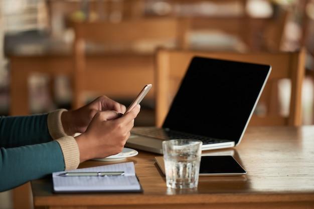 Handen van de onherkenbare man met behulp van smartphone in café en laptop op tafel