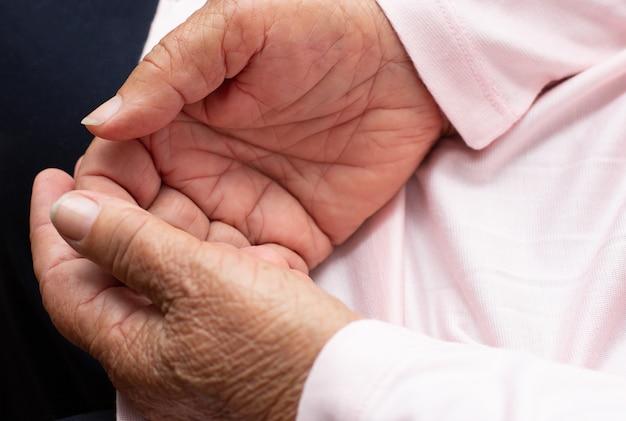 Handen van de oude vrouw.