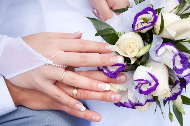 Handen van de pasgetrouwden met trouwringen