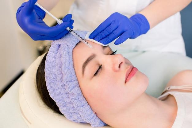 Handen van de schoonheidsspecialiste die botox in het vrouwelijke voorhoofd injecteert.
