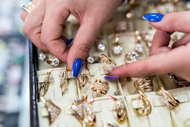 Handen van de verkoper die oorbellen in de goudwinkel tonen