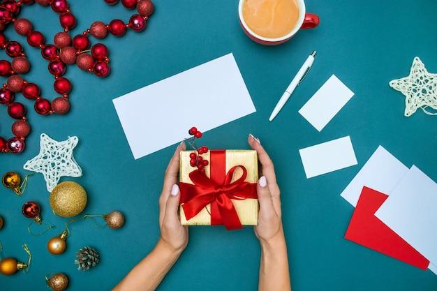 Handen van de vrouw en de doos van de kerstmisgift.