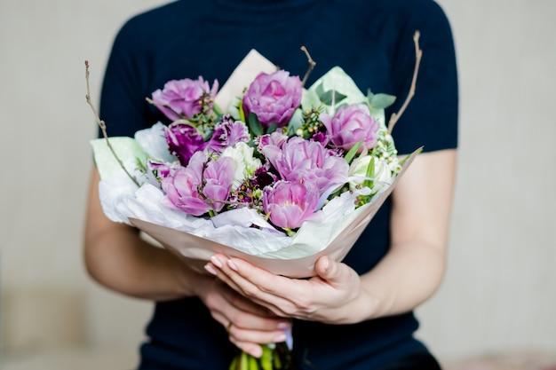 Handen van de vrouw met een bloeiende bloemboeket van verse roze tulpen, boterbloem, bladeren.