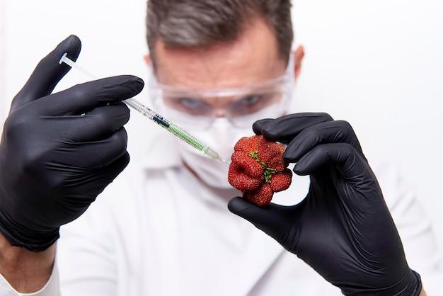 Handen van de wetenschapper in zwarte handschoenen met een spuit met injectie en aardbeien van ongebruikelijke vorm.