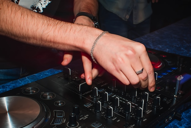 Handen van dj-mixer om de muziek in nachtclub te spelen