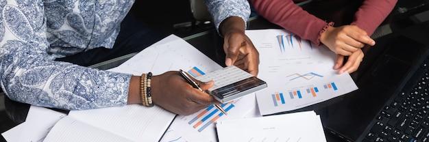 Handen van donkere mensen houden calculator tegen achtergrond van financiële documenten in bedrijfsruimteclose-up