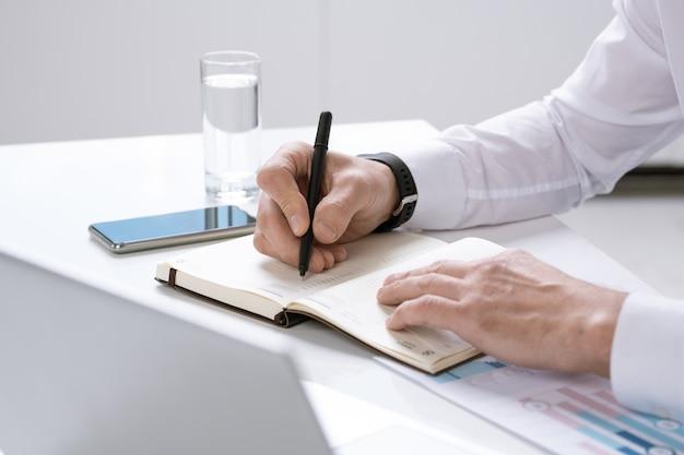 Handen van drukke hedendaagse ondernemer met pen over pagina van notitieblok werkplan opschrijven