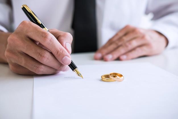 Handen van echtgenoot die echtscheidingsakte ondertekenen (ontbinding of opzegging)