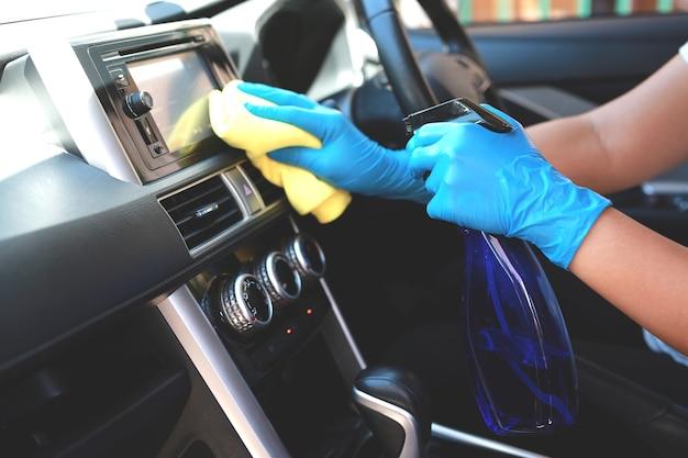 Handen van een autopoetser die een spuitbus en een doek gebruikt.