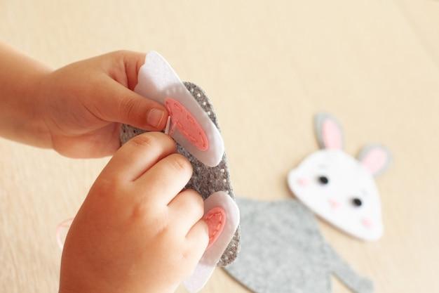 Handen van een babymeisje close-up, ze naait een konijnenspeeltje van vilt.